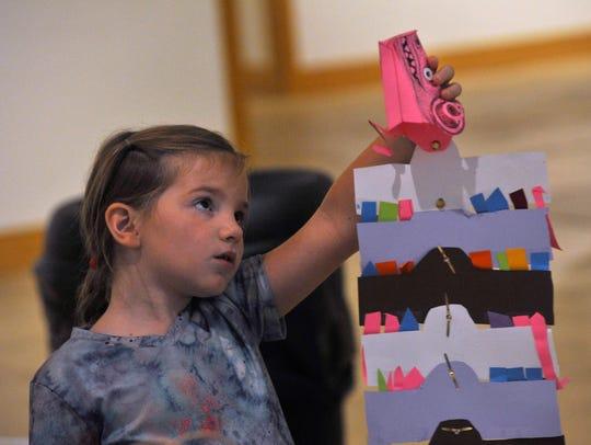 Madeline Stapp, 8, examines her Quetzalcoatl puppet