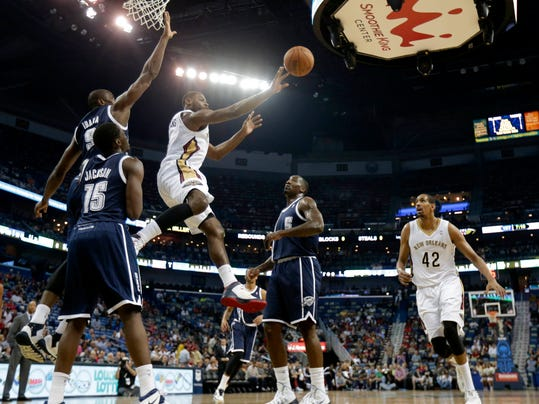 New Orleans Pelicans forward Tyreke Evans (1) passes between Oklahoma City Thunder forward Serge Ibaka (9), guard Reggie Jackson (15) and center Kendrick Perkins (5) in the first half of an NBA basketball game in New Orleans, Monday, April 14, 2014. Right is Pelicans center Alexis Ajinca (42). (AP Photo/Gerald Herbert)