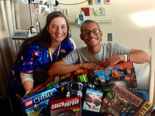 Jeffrey Brown gets board games a Lego set and Nerf gun in December 2013 at C.S. Mott Children's Hospital at the University of Michigan in Ann Arbor, where he underwent chemotherapy for brain cancer. Here, he's photographed with an unknown nurse who delivered the Christmas gifts.