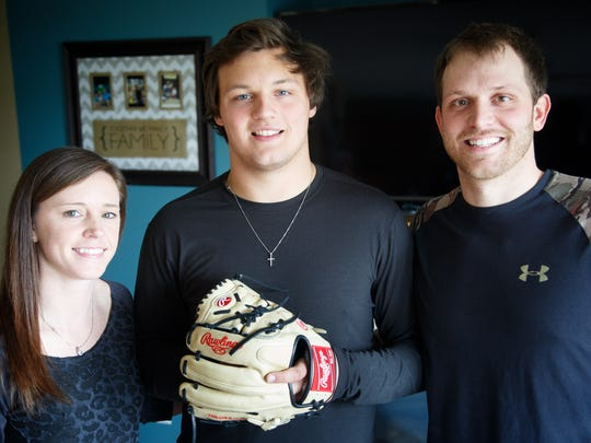 Tyler Lewis, center stands with his aunt and uncle Courtney and AJ Lewis at their home Friday, April 13, 2018.