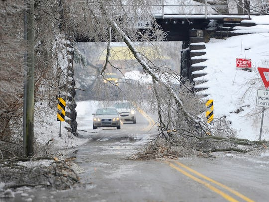 Cars drive under the railroad bridge on Emig Road in Manchester Township despite fallen tree braches on either side Wednessday, February 5, 2014. The road was closed but many drivers went around cones blocking the area. An overnight ice storm took down trees and cut power to thousands of York county residents. Eileen Joyce - Daily Record/Sunday News