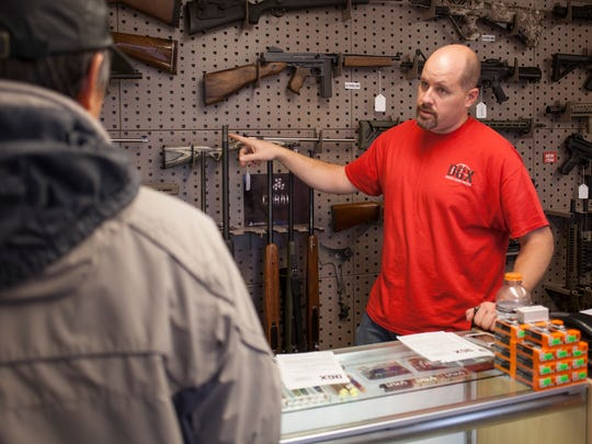 Chris Michel, Dixie Gun Worx Owner, discusses buying options with a customer Tuesday, Jan. 5, 2016.