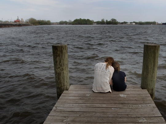 Ashley Behling (left) shares a quiet moment Thursday with her daughter, Kyla Friday, on a dock next to the Trestle Trail before a prayer service for the victims of last Sunday's shooting.