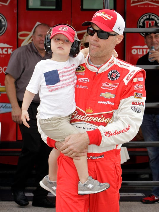 Kevin Harvick carries his son Keelan in the garage before NASCAR Sprint Cup Series auto racing practice Friday, Nov. 20, 2015, at Homestead-Miami Speedway in Homestead, Fla. (AP Photo/Darryl Graham)