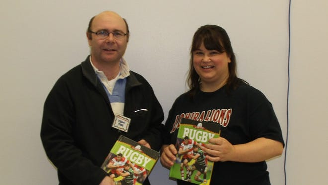 Benjamin Blanc, vice president of Fond du Lac Rugby, Inc with Heidi Tibbits, accepting two books for the Theresa Elementary Media Center and the Lomira Elementary and Middle school media center.