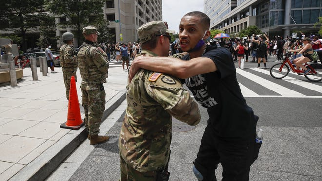 FILE - In this June 6, 2020, file photo, a demonstrator hugs a National Guard soldier during a protest  in Washington, over the death of George Floyd, a black man who was in police custody in Minneapolis. The National Guard has designated military police units in two states to serve as rapid reaction forces in order to be better prepared to respond quickly to civil unrest around the country, in the wake of the violent protests that rocked the nation's capitol and several states this summer.