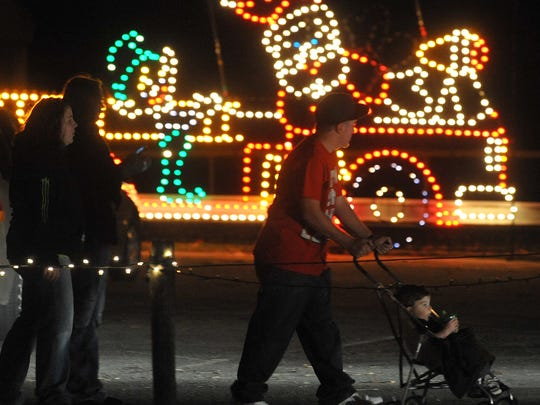 A family views Christmas lights in Creitz Park during