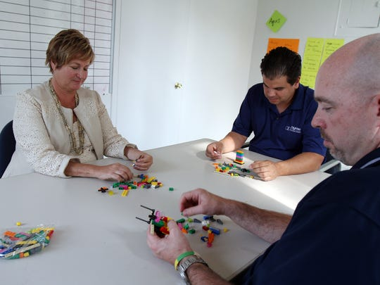 Maureen Ennis of Belmar, owner of Thrive, works with Lego bricks on a teambuilding activity with clients (right) Timothy Collins, president of DigiVac in Matawan, and (center) Mike Bodon, CEO of Aquis, based in Orlando, Florida, at the offices of DigiVac.