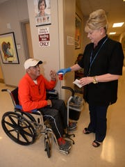 Cathy Nielson hands Keith Irbin a cup of coffee while visiting patients in one of the waiting areas at Feist Weiller Cancer Center. Nielson volunteeers her time at the facility handing out cookies and coffee and chatting with folks during, what for some is, a difficult time.