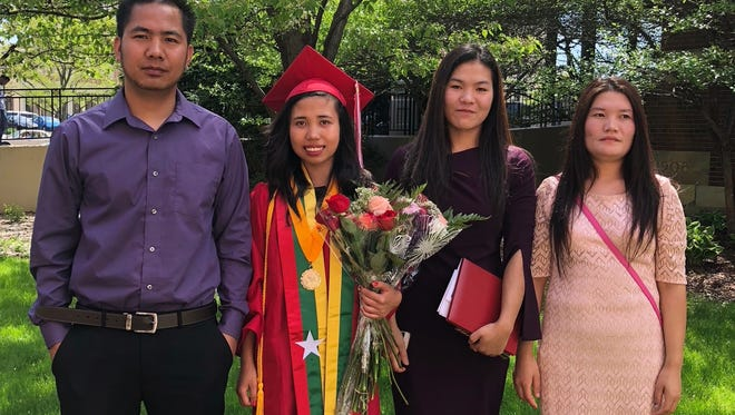 Dawt Iang is the 2018 valedictorian at Milwaukee's South Division High School and is among 900 MPS graduates who received college scholarships this year. Iang, pictured with family on her graduation day, fled Myanmar with her sister and spent eight years in Malaysia before coming to Milwaukee in 2015.