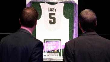 Attendees look at a Michigan State basketball jersey before a memorial to celebrate the life and legacy of Lacey Holsworth, an 8-year-old Michigan State basketball fan whose battle with cancer inspired the team's players, coaches and many more beyond the hardwood, Thursday at Michigan State University's Breslin Center in East Lansing.
