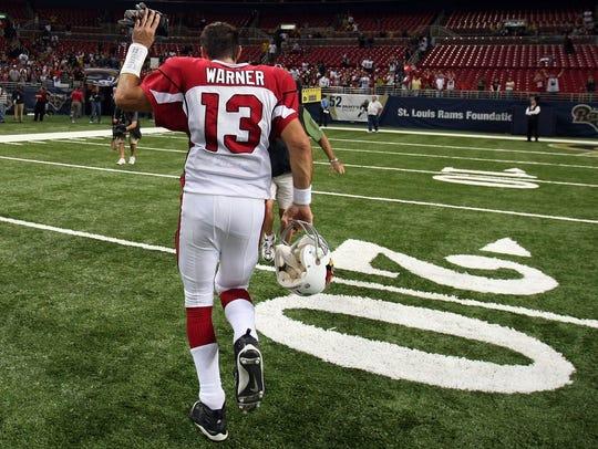 Cardinals quarterback Kurt Warner waves to fans as