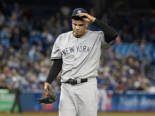 New York Yankees pitcher Dellin Betances walks off the mound after giving up two runs in the eighth inning of a baseball game against the Toronto Blue Jays, in Toronto on Saturday, March 31, 2018.