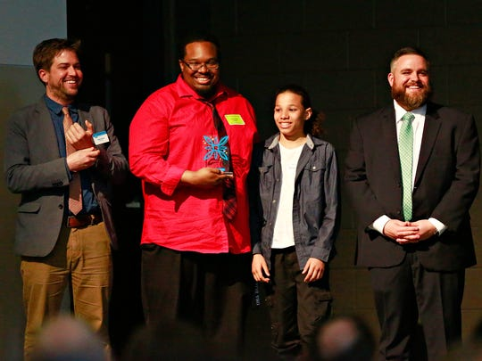 Antwoine Dorm, center left, and son Antwoine Dorm Jr., of Stick N Move Boxing, are shown with Dylan Bauer, left, and Silas Chamberlin, both of Downtown Inc., after receiving the award for Outstanding Nonprofit Organization during the 2018 Downtown First Awards at Logos Academy in York City, Thursday, April 12, 2018. Dawn J. Sagert photo
