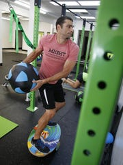 Bill Fredericks throws the medicine ball while standing on a balancing board as part of a fitness regime at Fit & Functional gym on Thursday, Aug. 6, 2015.