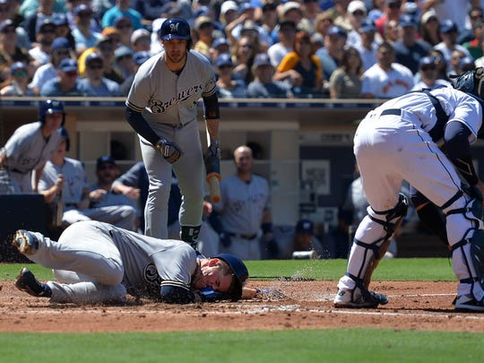 Brewers starting pitcher Chase Anderson scores on an awkward slide at Petco Park on Thursday in San Diego.