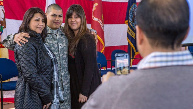 Pfc. Oscar A. Barrera, center, poses for a photo with his family after the Salute to Troops ceremony for the 328th Military Police Company, New Jersey Army National Guard, at the National Guard Armory in Cherry Hill Sunday. The company will deploy to Guantanamo Bay, Cuba, in support of Operation Enduring Freedom.