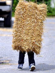 Tyler Measel carries a bale of straw during a previous