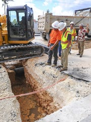 Felix Benavente, far right, Department of Public Works acting director, consults with engineers on options to repairing a section of roadway in East Hagatna on July 22.