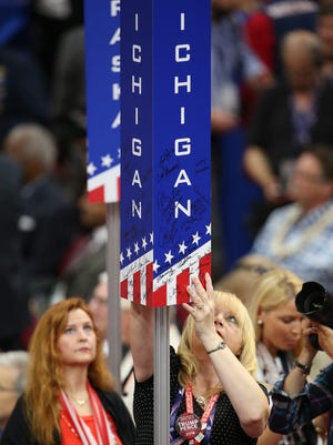 A delegate signs the Michigan sign during the first day of the 2016 Republican National Convention at Quicken Loans Arena in Cleveland, Ohio on July 18, 2016.