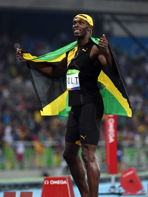 Usain Bolt soaks in the adoration after winning his third consecutive gold medal in the 100 meters.