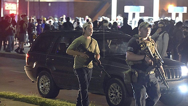 Kyle Rittenhouse, left, walks in Kenosha, Wis., Aug. 25 with another armed civilian. Prosecutors charged Rittenhouse in the fatal shooting of two protesters and the wounding of a third.