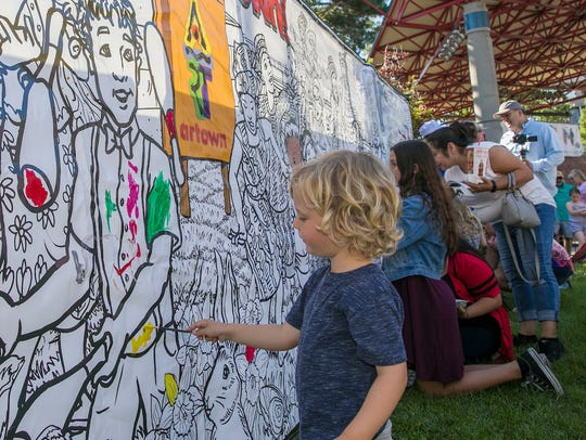 Three-year old Ranger paints on a mural during Artown's