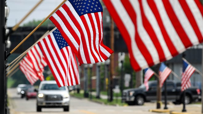 Traffic travels down Water Street as the Henderson central business district in lined with American flags for election day Tuesday, May 22, 2018.