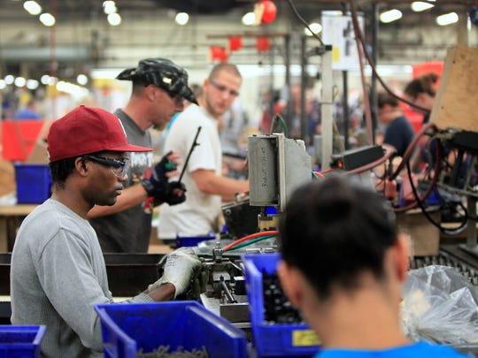 Workers assemble the 760 Pumpmaster air rifle on the line at Crosman Corporation in East Bloomfield.