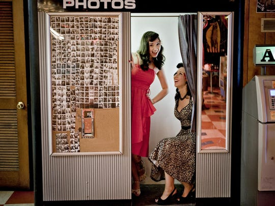 Sisters Monica and Ariel Lopez of Woodbridge take pictures together in the Asbury Lanes photo booth in 2011.