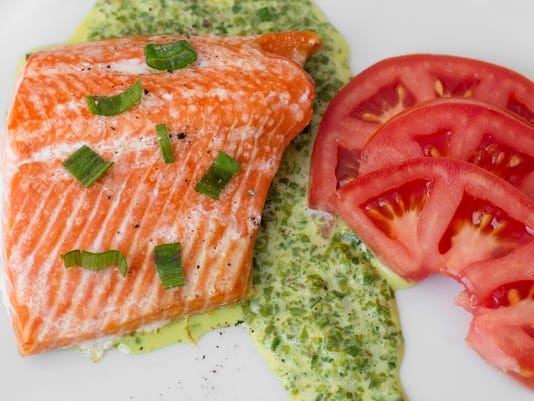 Oven-baked salmon served with green lettuce sauce and fresh tomatoes. Photo by Jeff Lautenberger.