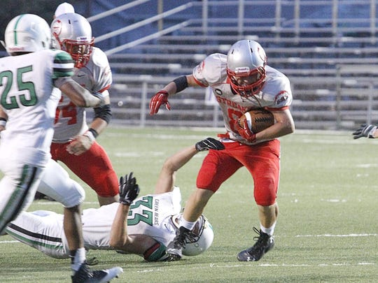 St. Joseph Central Catholic running back Ross Snyder breaks an Ottawa Hills tackle in a game last season.