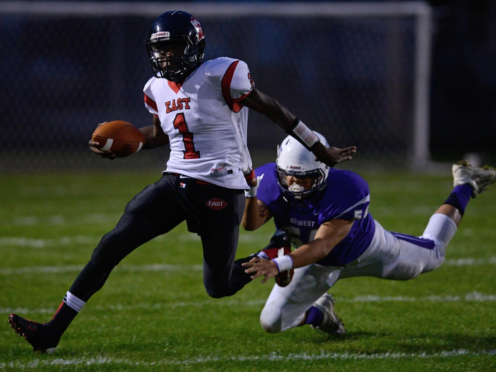 Green Bay East's Deonte Carlton tries to shake a tackle by Green Bay West's Tyler Chanthavong in a Bay Conference game last Friday. Carlton is second in the Bay with 498 rushing yards this season.