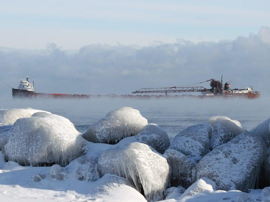 """""""Winter Arrival in Marquette,"""" by Rod Burdick. When the Laker Kaye E. Barker arrived at Presque Isle Harbor, Marquette, on a frigid December morning, """"The sea smoke on Lake Superior and iced-over rocks on the lakeshore caught my eye,"""" he said."""