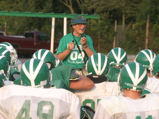 - - Text: Brick 8-16-04 Robert Ward/ Warren Wolf head footbal coach Brick high school talks to players during practice.
