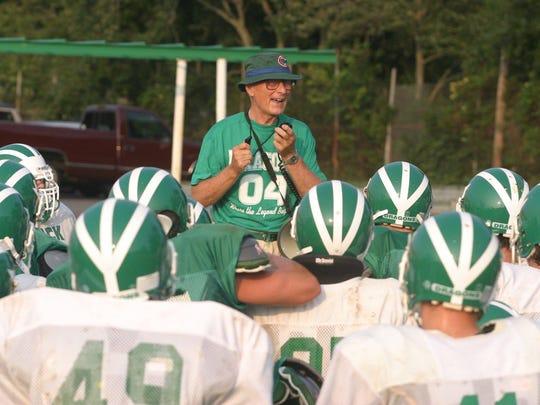 - - Text: Brick 8-16-04 Robert Ward/ Warren Wolf head footbal coach Brick high school talks to players during practice.