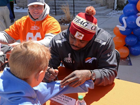 Denver Broncos defensive end Malik Jackson autographs a sweatshirt for a Broncos fan Monday at Windsor Town Hall. Tackle Mitch Unrein looks on. Denver Broncos players along with cheerleaders and Miles, the mascot, visited Windsor as part of the Broncos' Mile High Salute to Fans Tour.