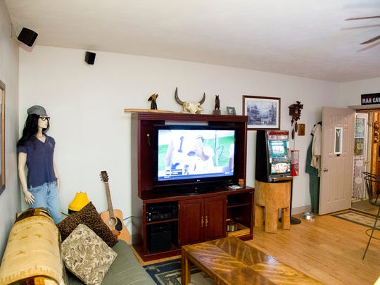 Jason Burks furnished his man cave with a 52-inch television, games and a mannequin that his daughters dress according to the theme of the current get-together.