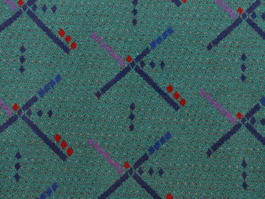 The Port of Portland partnered with SRG Partnership, Inc., of Portland in the late 1980s to design the existing PDX carpet. The pattern symbolized what an air-traffic controller would see from the control tower at night, such as runways and lights, and used colors.