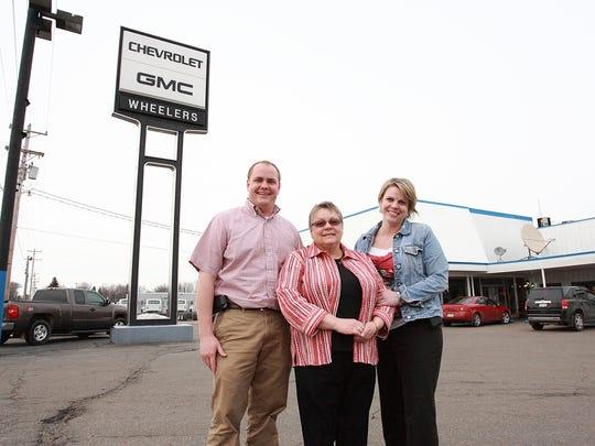 From left: Daniel Wheeler, Ann Wheeler and Mary Jo Wheeler-Schueller stand outside their Marshfield car dealership. Ann Wheeler soon will acquire two Wisconsin Rapids dealers.