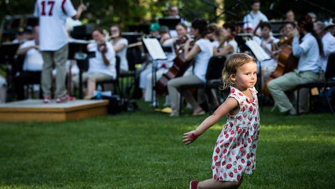 Children dance on the lawn as the MSO performs sports-themed music during Festival on the Green Saturday evening.