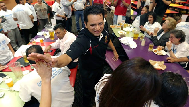 SISD Superintendent Jose Espinoza high fives supporters after seeing early voting results for the district's $448.5 million bond election Tuesday night at Peter Piper Pizza in Socorro. The bond measure passed.