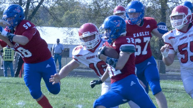 Wellsville junior running back Jacob Hunsaker attempts to run away from Osage City defenders Saturday in the 45-20 loss.