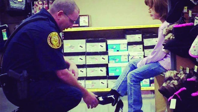 A Fairview police officer helps a child pick out shoes during a previous Shop With a Cop  grand finale shopping day.