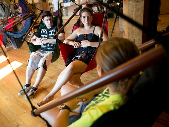 From left, University of Wisconsin - Stevens Point students Evan Walters, 23, Ashley Kiesow, 22, and Sarah Madden, 22, sits in the swings during the grand opening of Sunset Point Winery in Stevens Point, Friday, Sept. 4, 2015.