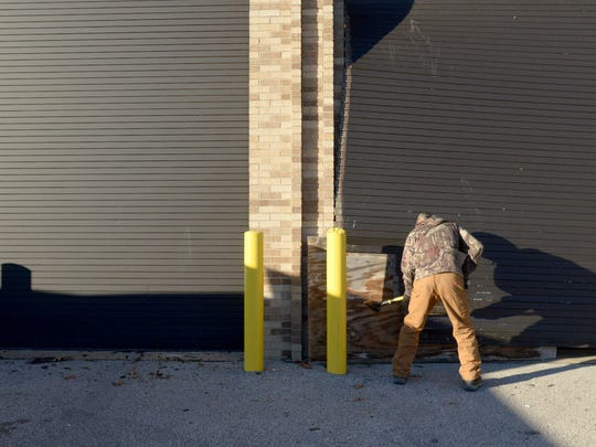 Larry Watts uses an ax to remove the bottom panels of a garage door at Crockett County High School's vocational building Thursday. An EF-1 tornado touched down in the area causing damage to parts of the school on Tuesday.