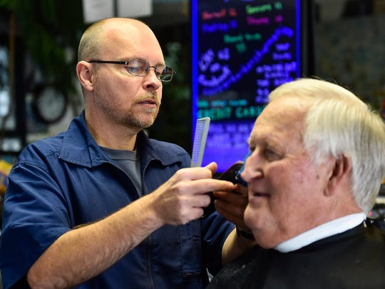 Chris Owens, the owner and the barber at, The Corner Barber Shop, gives loyal customer Jerry Hall a trim on Thursday morning.