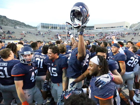 UTEP offensive lineman Jerrod Brooks, 72, raises his helmet as the team celebrated their 52-24 victory over North Texas Saturday in the Sun Bowl. Miner running back Aaron Jones, foreground, broke the schools yards rushing record for a single season during the game.