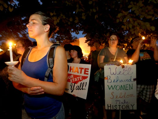 Jennifer Samardak, left, attends a candlelight vigil