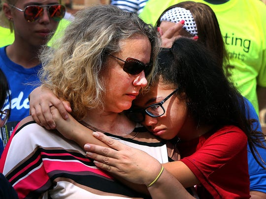 Michelle Edralin, right, hugs her mom, Brandi Davison-Edralin, at a June 8, 2018, rally for her father, Cloyd Edralin, on the steps of the Reformed Church of Highland Park, New Jersey. He is a father of four who was picked up June 4, 2018.